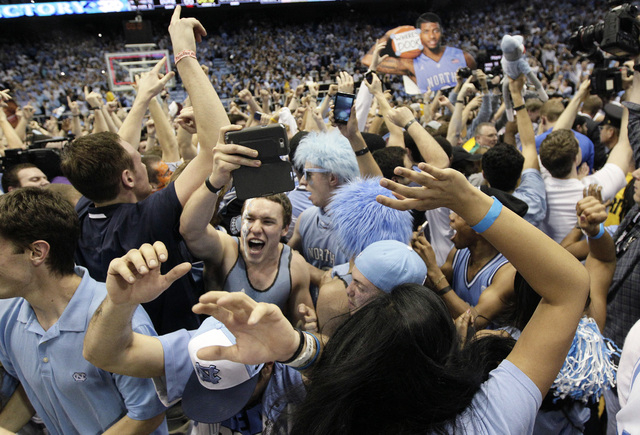 Fans rush the playing court following North Carolina's 74-66 win over Duke in an NCAA college basketball game in Chapel Hill, N.C., onThursday. (AP Photo/Gerry Broome)