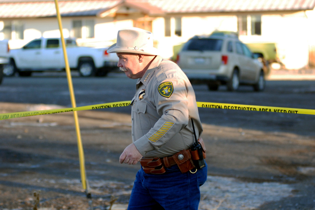 Modoc County Sheriff and Coroner Mike Poindexter ducks under crime scene tape Friday, Feb. 21, 2014 outside the tribal headquarters of the Cedarville Rancheria in Alturas, Calif., where local medi ...