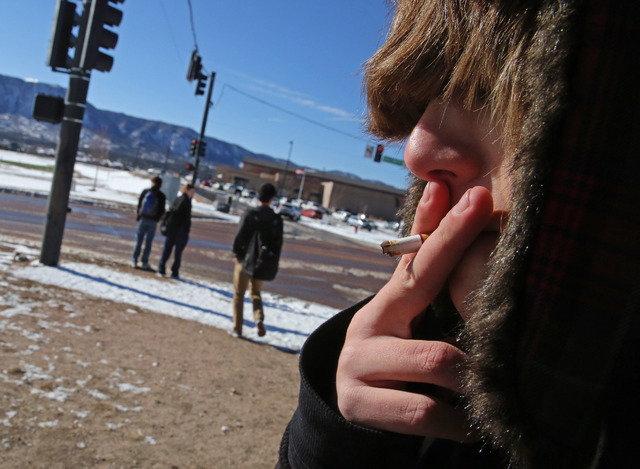 A high school student, who preferred not to be identified, smokes a cigarette in a de facto smoking area just off the property of Lewis-Palmer High School, in Monument, Colo., Thursday Feb. 20, 20 ...