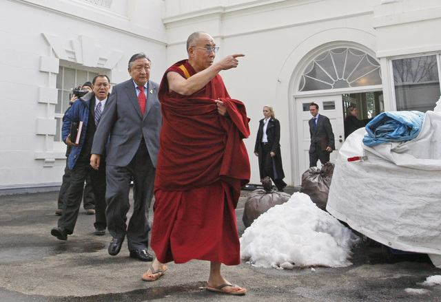 FILE - In this Feb. 18, 2010, file photo, The Dalai Lama walks out of the White House in Washington, after meeting with President Barack Obama. Obama will host Tibetan spiritual leader the Dalai L ...