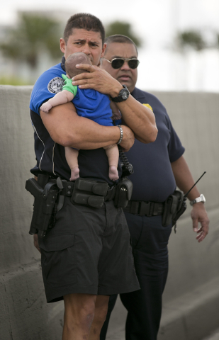 Sweetwater officer Amauris Bastidas keeps a watchful eye waiting for paramedics after aiding a 5-month-old Sebastian de la Cruz who stopped breathing. The baby's aunt performed CPR after pulling h ...