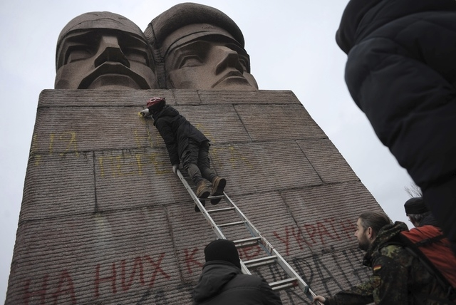 People paint on the KGB officers monument in Kiev, Ukraine, on Sunday. A top Ukrainian opposition figure assumed presidential powers Sunday, plunging Ukraine into new uncertainty after a deadly po ...