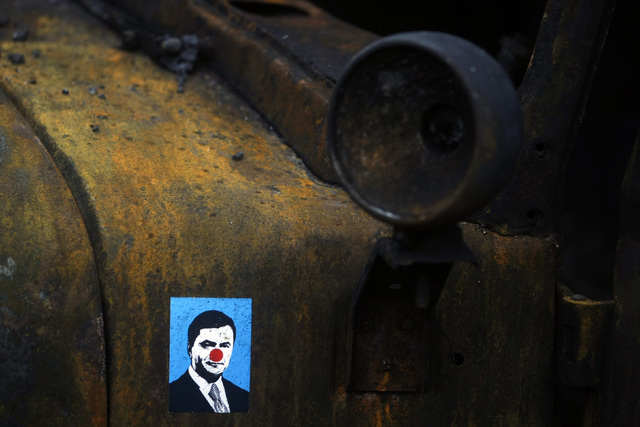 A sticker depicting Ukrainian President Viktor Yanukovych is placed on a burned military truck in Kiev, Ukraine, on Sunday. The Kiev protest camp at the center of the anti-President Viktor Yanukov ...
