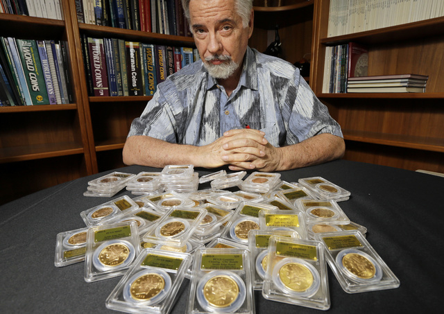 David Hall, co-founder of Professional Coin Grading Service, poses with some of 1,427 Gold-Rush era U.S. gold coins, at his office in Santa Ana, Calif., Tuesday, Feb. 25, 2014.  A California coupl ...