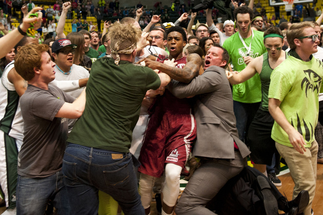 In this Thursday, Feb. 27, 2014 photo, New Mexico State's Daniel Mullings, at center in red and white jersey, is involved in a brawl involving players and fans who came onto the court when New Mex ...