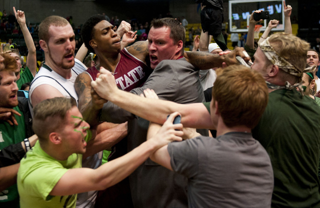 In this Thursday, Feb. 27, 2014 photo, New Mexico State's Daniel Mullings, center left in red and white jersey, is involved in a brawl involving players and fans who came onto the court when New M ...