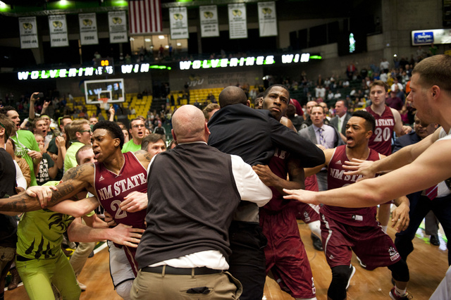 In this Thursday, Feb. 27, 2014 photo, security, at center back to camera, try to hold back players as a wild brawl involving players and fans who came onto the court broke out when New Mexico Sta ...