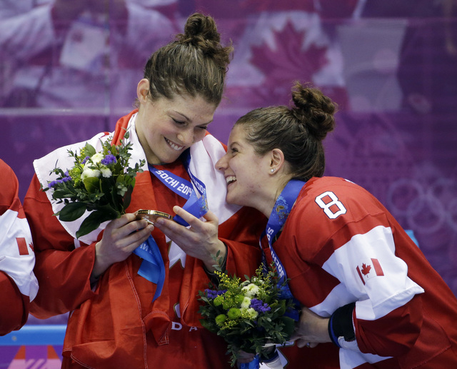 Members of team Canada react while receiving their gold medals after beating the USA 3-2 in overtime of the gold medal women's ice hockey game at the 2014 Winter Olympics, Wednesday, Feb. 19, 2014 ...