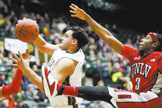 Colorado State's J.J. Avila, center, and UNLV's Kevin Olekaibe come down from the basket during the second half of an NCAA college basketball game Wednesday, Feb. 5, 2014, at Moby Arena in Fort Co ...