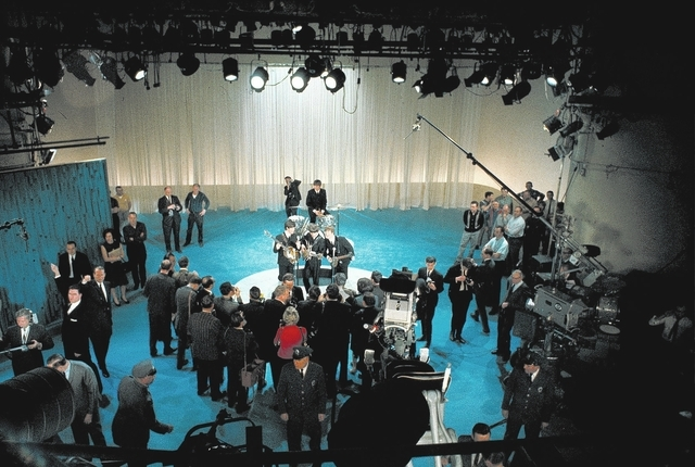 The British rock and roll group the Beatles, center, are surrounded by photographers on stage at CBS' Studio 50 before their live television appearance on The Ed Sullivan Show in New York City, Fe ...
