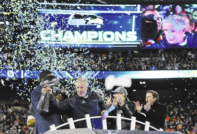 Seattle Seahawks head coach Pete Carroll holds the Vince Lombardi Trophy as he celebrates after the NFL Super Bowl XLVIII football game against the Denver Broncos Sunday, Feb. 2, 2014, in East Rut ...