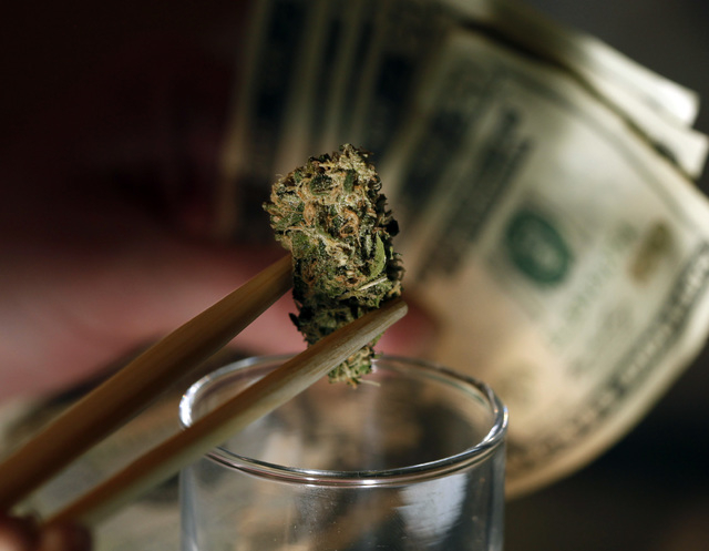 A caregiver picks out a marijuana bud for a patient at a marijuana dispensary in Denver. (AP Photo/Ed Andrieski)
