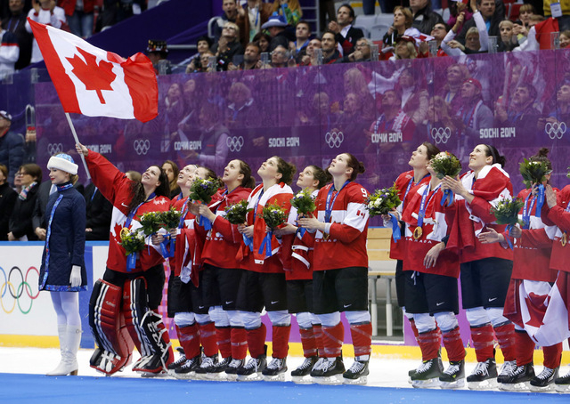 Team Canada sings the Canadian national anthem after receiving their gold medals after beating the USA 3-2 in overtime of the women's gold medal ice hockey game at the 2014 Winter Olympics, Friday ...