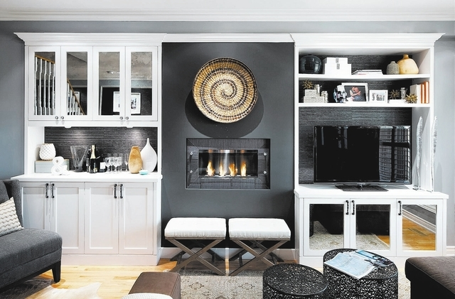 Working down the room's longest wall, a gorgeous ethanol fireplace was installed beside the TV. It was finished up with more custom cabinetry housing a bar. The cabinets feature open shelving to s ...