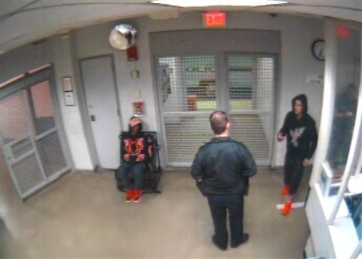 In this Jan. 23, 2014 video frame grab released by the Miami Beach Police Department, shows singer Justin Bieber, right, as he gestures to a police officer while under arrest at the Miami Beach po ...