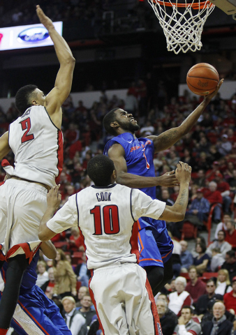 Boise State's Mikey Thompson (1) drives past UNLV's Khem Birch (2) and Daquan Cook (10) during their basketball game at the Thomas & Mack Center in Las Vegas on Saturday, Feb. 1, 2014. (Jason Bean ...