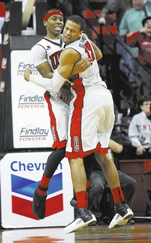 UNLV's Bryce Dejean-Jones (13) and Kevin Olekaibe (3) celebrate Olekaibe's go ahead three point shot over Boise State during their basketball game at the Thomas & Mack Center in Las Vegas on Satur ...
