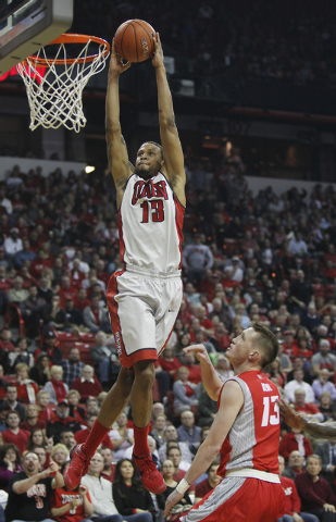 UNLV's Bryce Dejean-Jones (13) dunks over New Mexico's Cullen Neal (13) during their basketball game at the Thomas & Mack Center in Las Vegas on Wednesday, Feb. 19, 2014. (Jason Bean/Las Vegas Rev ...