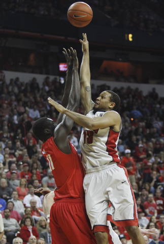 UNLV's Bryce Dejean-Jones (13) shoots over New Mexico's Obij Aget (11) during their basketball game at the Thomas & Mack Center in Las Vegas on Wednesday, Feb. 19, 2014. (Jason Bean/Las Vegas Revi ...