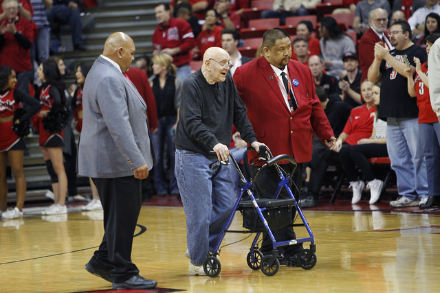 Hall of Fame coach Jerry Tarkanian gets escorted across Jerry Tarkanian Court to his seat before UNLV takes on New Mexico at the Thomas & Mack Center in Las Vegas on Wednesday, Feb. 19, 2014. (Jas ...