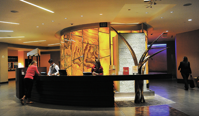 Cesar Macias, second left, helps Rebecca Vance, of New Orleans, at the front desk at the Canyon Ranch Spa in the Palazzo hotel-casino in Las Vegas, Thursday, Feb. 7, 2014. At right, is employee Bl ...