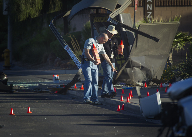 A Las Vegas police officers investigate a two-vehicle accident at the intersection of Bonanza Road and Lamb Boulevard on Friday, Sept . 20,2013 morning.  Three children are in critical condition w ...