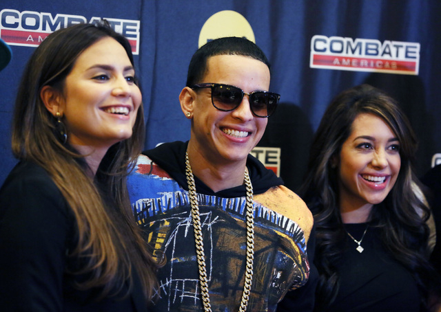 Combate Americas co-producer Gabriela Cocco-Sanchez, from left, commissioner Daddy Yankee and co-host Andrea Calle stand for photos for a Combate Americas press conference and luncheon at the Vene ...