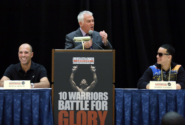 Ultimate Fighting Championship fighter Royce Gracie, from left, UFC co-founder and founder of Combate Americas Campbell McLaren, and Combate Americas commissioner Daddy Yankee participate in a Com ...