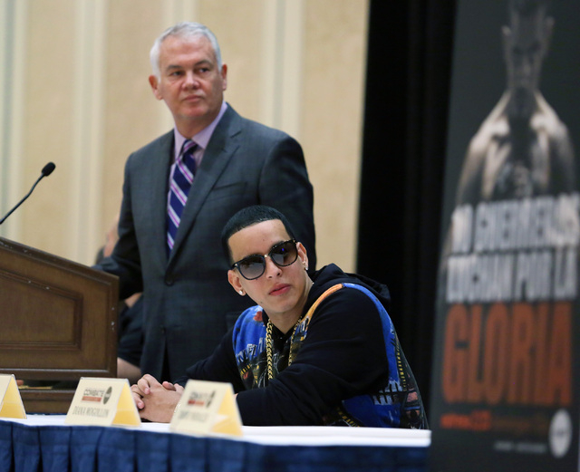 Ultimate Fighting Championship co-founder and founder of Combate Americas Campbell McLaren, back, Combate Americas commissioner Daddy Yankee watch a televsion show clip during a Combate Americas p ...
