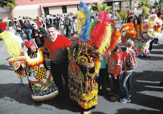 Elena Uriostegui, left, and Arturo Uriostegui, right, pose for a picture with Nevada Governor Brian Sandoval, center, before the beginning of the Chinese New Year parade on 4th Street in Las Vegas ...