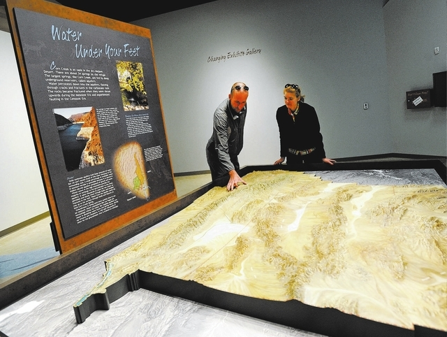 Brandon Lindsey, left, and Marisa Peterson examine a relief map inside the newly open visitor center at the Desert National Wildlife Refuge on Sunday, Dec. 29, 2013. The center at the Corn Creek f ...
