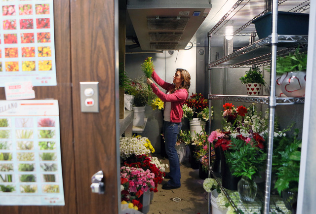 Liz Arthur makes selections from a walk-in cooler on Monday for an arrangement at A Country Rose, 290 E. Horizon Dr., Henderson. Owner Nikki Hays estimates that A Country Rose will distribute some ...