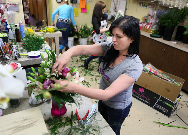 A worker, who identified herself only as Lily works on an arrangement Monday at A Country Rose,  290 E. Horizon Dr., Henderson. Owner Nikki Hays estimates that A Country Rose will distribute some  ...
