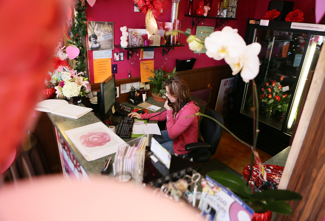 Liz Arthur speaks with a customer on the phone Monday at A Country Rose, 290 E. Horizon Dr., Henderson. Owner Nikki Hays estimates that A Country Rose will distribute some 3,500 roses and 400 stem ...