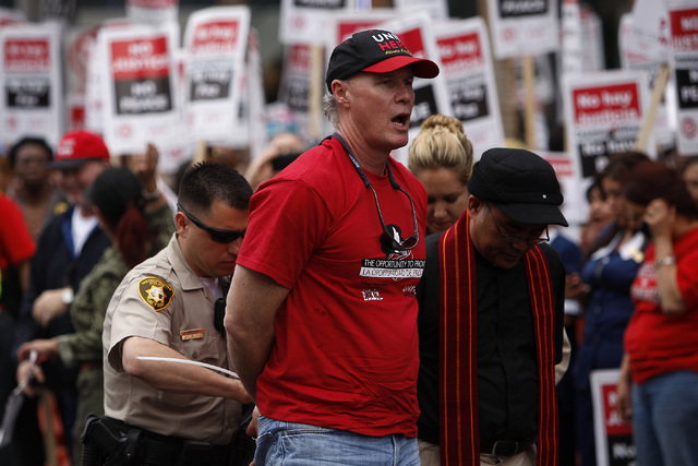 """In an act of civil disobedience, Donald """"D"""" Taylor, President of UNITE HERE, gets arrested on the Las Vegas Strip in front of the Cosmopolitan Hotel during a planned protest on March 20, 2013. (Ja ..."""