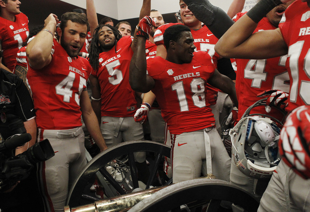 UNLV players dance over the Fremont Cannon as they celebrate their victory over UNR at Mackay Stadium in Reno on Oct. 26, 2013. (Jason Bean/Las Vegas Review-Journal)