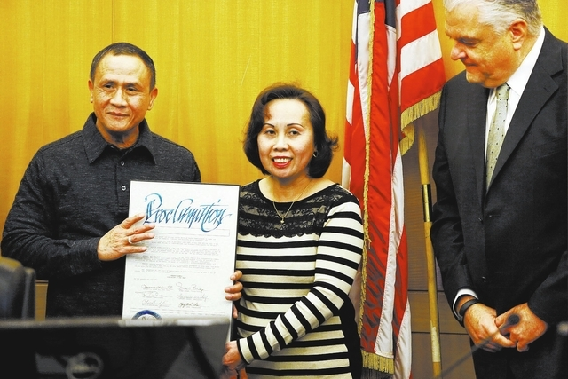 """Gerardo Gamboa, left, stands with his wife Elsa during a recognition ceremony declaring him """"Cab Driver of the Year"""" by Clark County Commission Chairman Steve Sisolak, right, at a coun ..."""