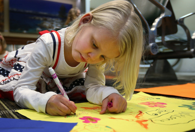 Eva Allen, 5, makes a welcome home poster while waiting for Nevada Army Guard soldiers at the Reno-Tahoe International Airport in Reno, Nev., on Sunday, Feb. 16, 2014. Allen's cousin was among the ...