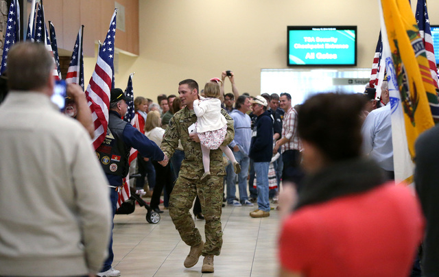 Carrying his niece Scarlet Harrison, Chief Warrant Officer II Josh Groth and fellow Nevada Army Guard soldiers walk through the Reno-Tahoe International Airport in Reno, Nev., on Sunday, Feb. 16,  ...