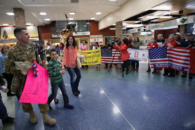 Chief Warrant Officer III Ian Dasmann and his family walk through the Reno-Tahoe International Airport in Reno, Nev., on Sunday, Feb. 16, 2014. About 300 supporters greeted the Nevada Army Guard s ...