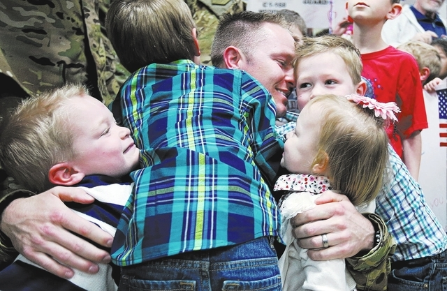 Lt. Nigel Harrison gets a group hug from his children, Jack, Halen, Scarlet and Beckham as he and fellow Nevada Army Guard soldiers arrive at the Reno-Tahoe International Airport in Reno, Nev., on ...