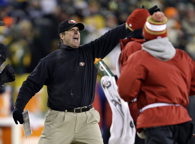 San Francisco 49ers head coach Jim Harbaugh directs his team during the first half of an NFL wild-card playoff football game against the Green Bay Packers, Sunday, Jan. 5, 2014, in Green Bay, Wis. ...
