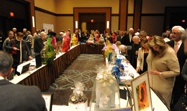 Guests look at the items up for auction at the Catholic Charities of Southern Nevada 73rd anniversary celebration Heart of Hope awards ceremony at the Red Rock Resort hotel-casino in Las Vegas, Fr ...