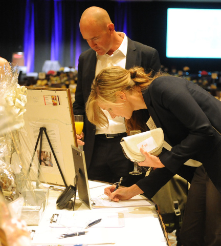 Linda McHale places a bid while Will Holliday watches during the silent auction at the Catholic Charities of Southern Nevada 73rd anniversary celebration Heart of Hope awards ceremony at the Red R ...