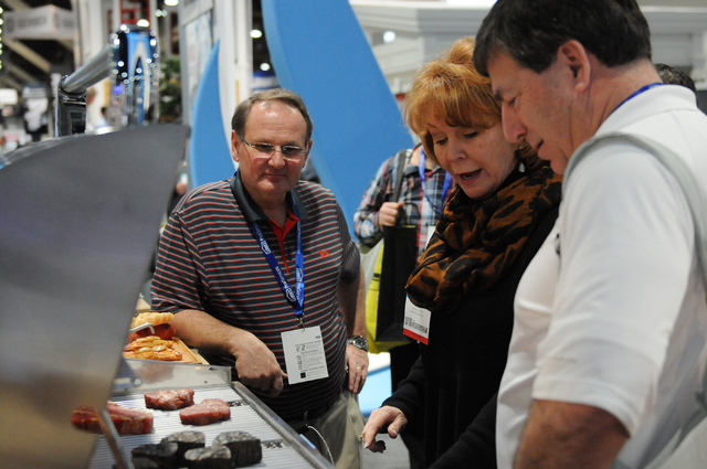 Shirley Byrd, center, sales representative for Fire Magic, demonstrates one of their outdoors grills to Guy Bonneville, left, and Brian Sicard during the International Builders' Show at the Las Ve ...