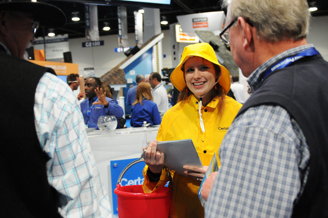 Saskia Bankert, center, promoter for CertainTeed, passes out flyers for their insulation product, Smartbatt, during the International Builders' Show at the Las Vegas Convention Center on Wednesday ...
