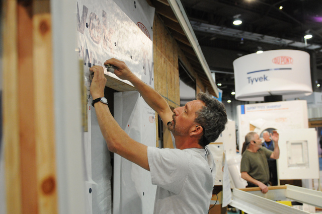 Mike Guertin demonstrates Tyvek, a water-resistive barrier material manufactured by DuPont, during the International Builders' Show at the Las Vegas Convention Center on Wednesday. (Erik Verduzco/ ...