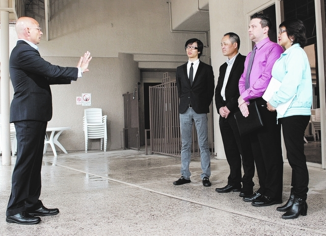 Anthony meets with management of the Fortune Hotel about the importance of budgeting. Owner Huiyan Chang (black suit) and GM Justin Campese (purple shirt) credit Travel Channel