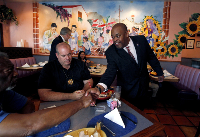 Niger Innis shakes hands with North Las Vegas Constable Herb Brown, not pictured, while Tom Jeeves, left, waits to hear Innis speak at the Hispanics in Politics at Dona Maria Tamales restaurant in ...