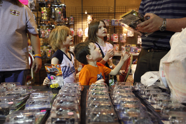 From left, Sydney Ivy, Marcus Ivy and Sophia Ivy look at their father Mark Ivy as he opens up toys he bought at the World of Toys Expo at the Plaza in Las Vegas Friday, Feb. 21, 2014. On the left  ...